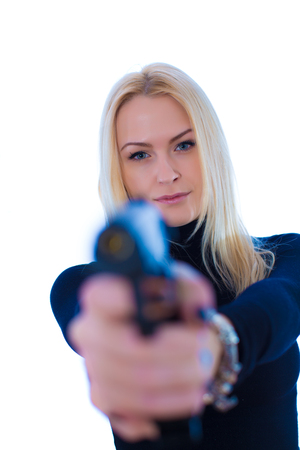 aiming: blonde girl in a black suit with gun aiming at camera Stock Photo