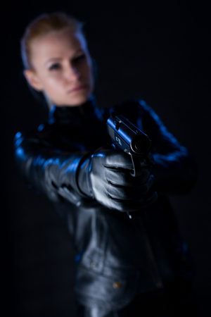 A young woman dressed in a black jacket with a gun in his hand on a black background