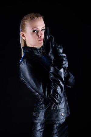mujer con pistola: Una mujer joven, vestido con una chaqueta de color negro con una pistola en la mano sobre un fondo negro