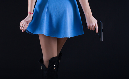 La muchacha en alineada con el arma en la mano