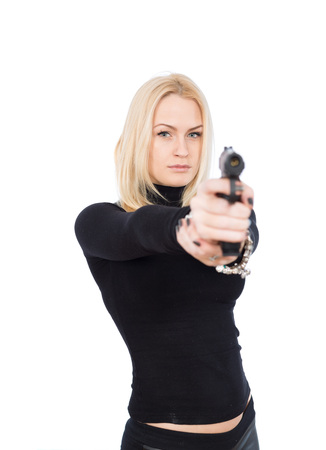 blonde girl in a black suit with gun aiming at camera Stock Photo