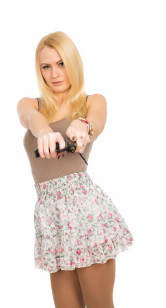Blonde young woman wearing skirt with gun in hand