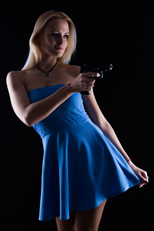 weapon: A woman wearing blue dress in sunglasses with gun on black background Stock Photo