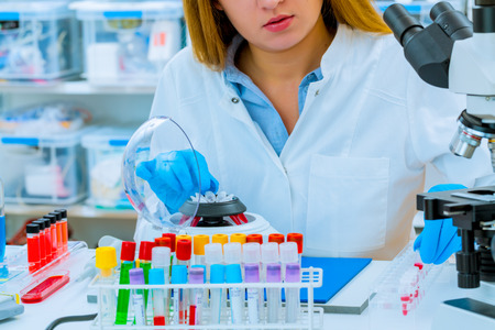 Mujer auxiliar de laboratorio de ensayo de PCR establece micro tubos en una centrifugadora.