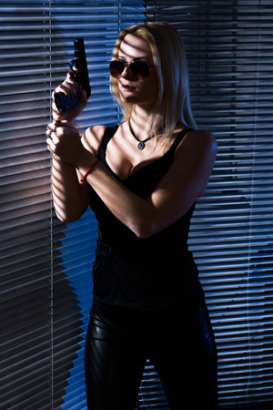 hidden danger: girl secret agent with gun hidden behind jalousie