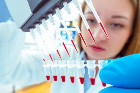 woman assistant in laboratory with multi pipette in the clinic, the research of cancer stem cells Foto de archivo