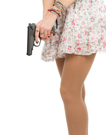 girl dressed in a short skirt with flowers holding a gun