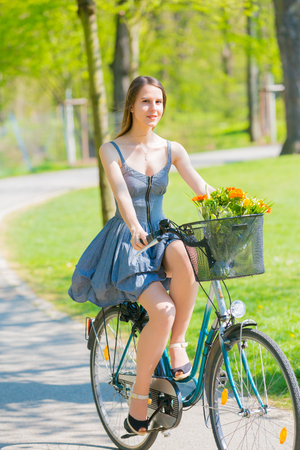young adult woman: Young pretty woman riding bike in park Stock Photo