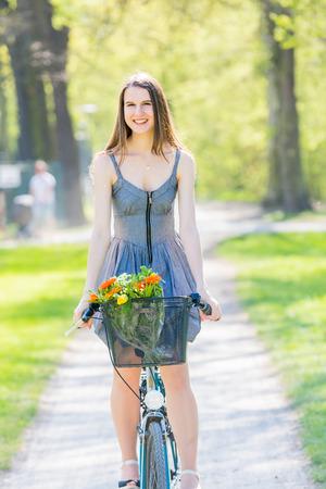 mujer bonita: Mujer bonita joven que monta en bicicleta en el parque