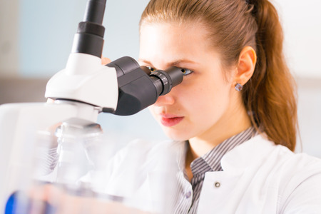 medical person: young woman. laboratory assistant watching biological experiment