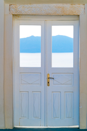 view of a wooden doorway: Beautiful white wooden door above aegean sea in Oia, Santorini, Cyclades, Greece