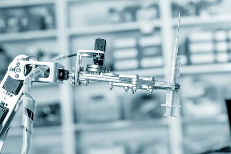 Medical syringe in roboter hand Reklamní fotografie