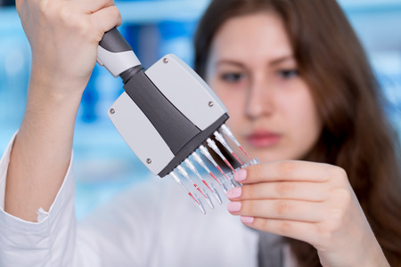 research science: Woman technician with multipipette in genetic laboratory