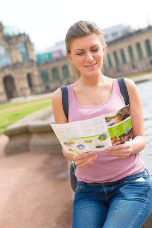 travel guide: Female tourist reading a travel guide Stock Photo