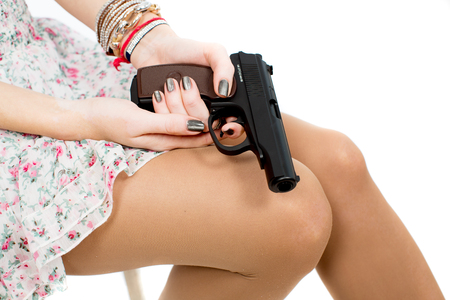 A girl holding a gun on her lap