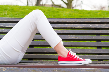 lays: The girl lays on a bench wearing sneakers Stock Photo