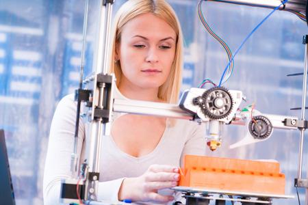 adjusting: Young woman adjusting 3d printer Stock Photo