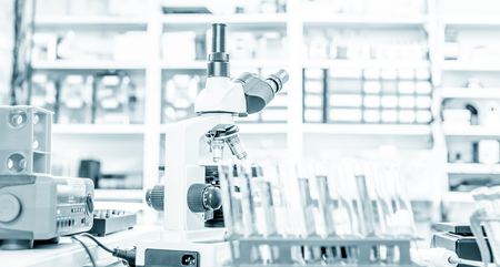sample tray: Microscope and test tubes on laboratory bench Stock Photo