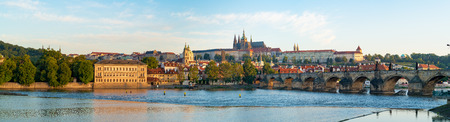 st charles: Panorama of Prague with Vltava river in the foreground, Charles Bridge on right and St.   Vitus Cathedral on the horizon. City Panorama at sunrise on a summer day Stock Photo