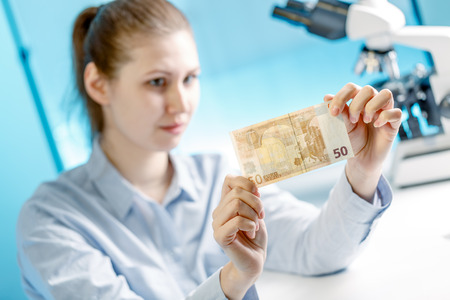 evidence bag: Woman checks the authenticity of Euro banknotes money in a laboratory
