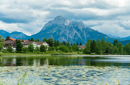 sky reflection: Lake in the German Alps with a chain of mountain peaks on the horizon. Reflection of the sky in water Stock Photo