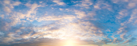 panorama of the sky during sunset or sunrise with cumulus clouds colored orange by the sun. Foto de archivo