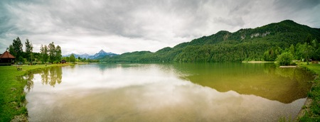 horizon reflection: Lake in the German Alps with a chain of mountain peaks on the horizon. Reflection of the sky in water Stock Photo