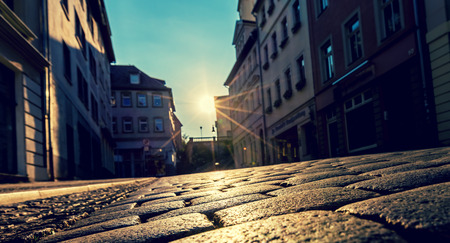 city of sunrise: Sunrise in a city street with paving stones Stock Photo
