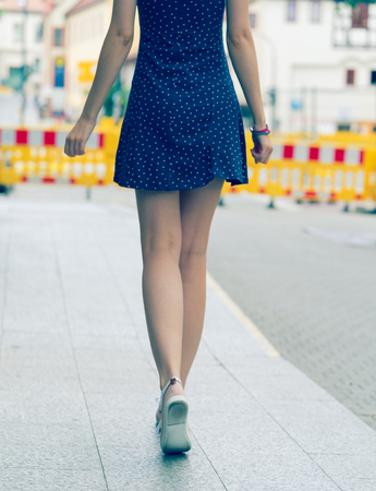 summer dress: Pretty girl with long hair wearing a short dress in the city. Toned photo. Young woman stands with his back to the camera