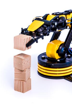 manipulator: Plastic model of industrial robotics arm  Robot manipulator with toy cube