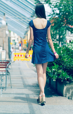 Pretty girl with long hair wearing a short dress in the city. Toned photo. Young woman get out with his back to the camera