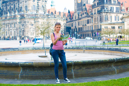 guid: Young woman read travel guid in Dresden. Germany