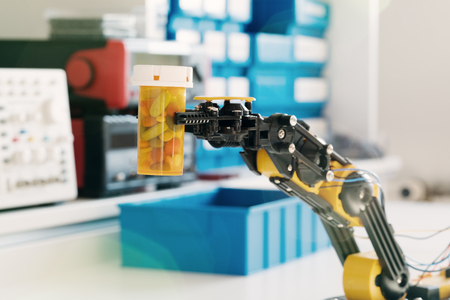 manipulator: Plastic model of industrial robotics arm Robot manipulator and vial with pills Stock Photo