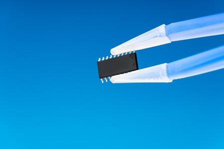 silicon: microchip ic en pinzas, chip de silicio con una red neuronal artificial