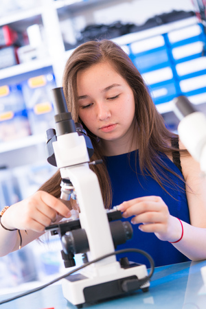microscope slide: Teen school girl in biological lesson using binocular microscope with microscope slide in hand Stock Photo