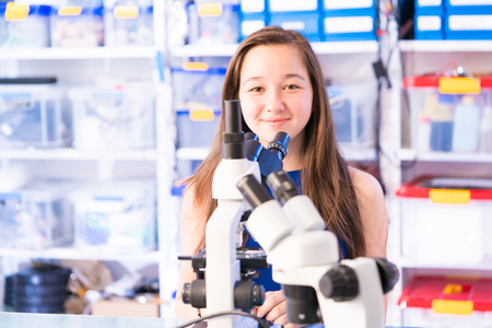 Biology lesson. Female Teenage Student In Science Class With Experiment on Microscope Stock Photo