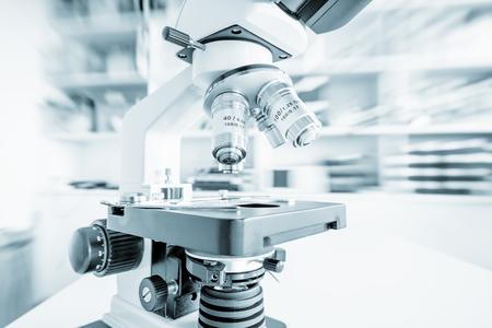 Wetenschapsmicroscoop op laboratoriumbank. Laboratorium voor microbiologie. Blauw gestemd beeld van binoculaire microscoop