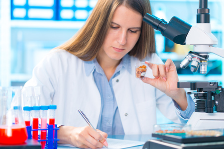 Research GM in microbiological laboratory. Young woman researcher Stock Photo