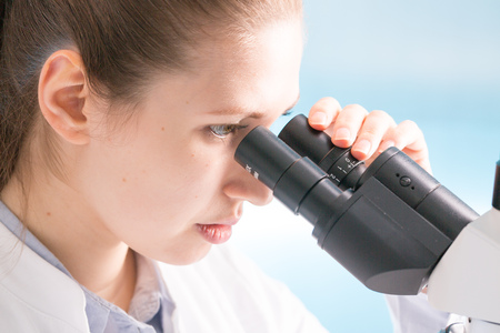 pathologist: Young woman student work in microbiological laboratory with microscope