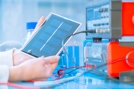 schoolgirl with solar cell in hand in physics classroom Stock Photo