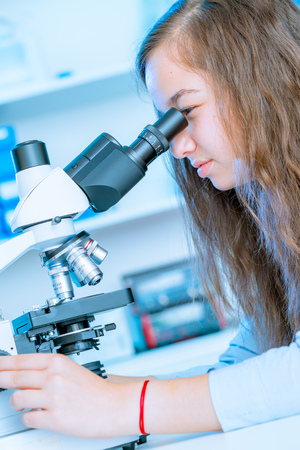 Young woman student work in microbiological laboratory with microscope