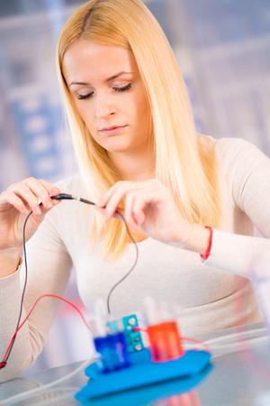 Frau Wissenschaftler mit Wasserstoff-Brennstoffzelle im Labor