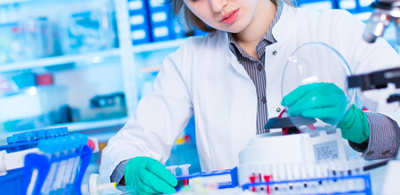 pcr: Young woman work with PCR centrifuge in laboratory