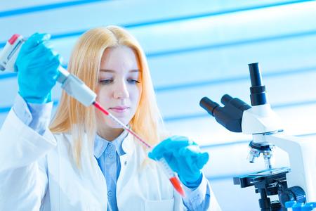 pcr: Young woman technician use pipette in laboratory