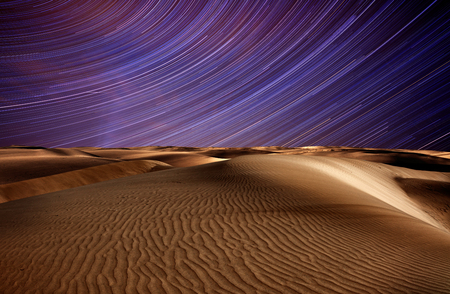 Night in the desert sand dunes and star trails on blue night sky