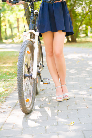 falda corta: Long legs of a girl wearing a short skirt next to a bicycle. Bike and legs