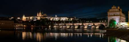 Panorama of Prague with Vltava river in the foreground, Charles Bridge on right and St. Vitus Cathedral on the horizon. Night skyline Stock Photo