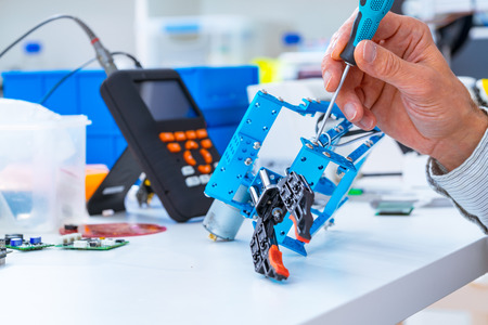 Robotics development closeup. Electronics engineer or programmer hands with special tools working with robot arm. Modern technologies. DIY Hobby Concept