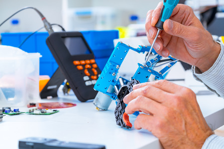component: Robotics development closeup. Electronics engineer or programmer hands with special tools working with robot arm. Modern technologies. DIY Hobby Concept