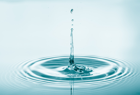 Water drop falling and drips on water mirror. Drops splash and make perfect circles on water surface